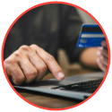 man typing on keyboard with credit card in hand